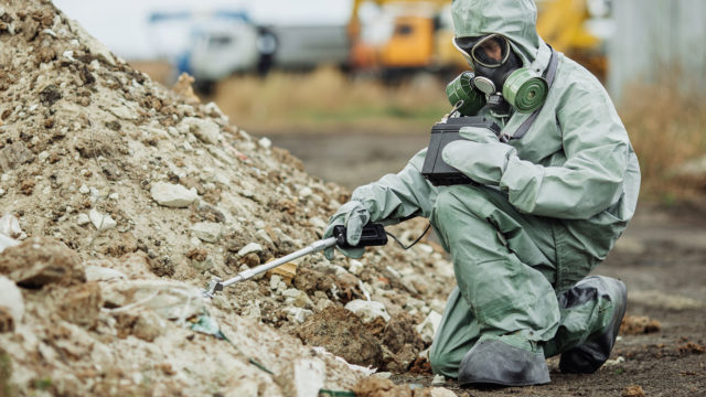 Photo of person in hazmat suit at rubble pile using tool to analyze soil